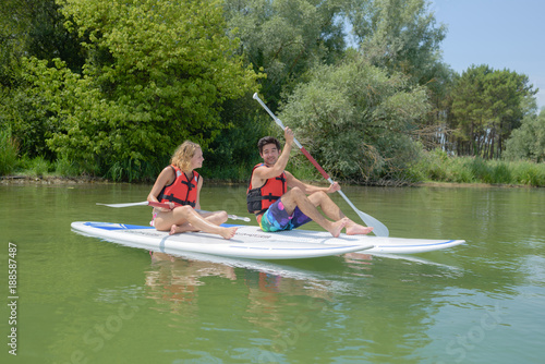 Foto Murales Couple paddling on boards in river