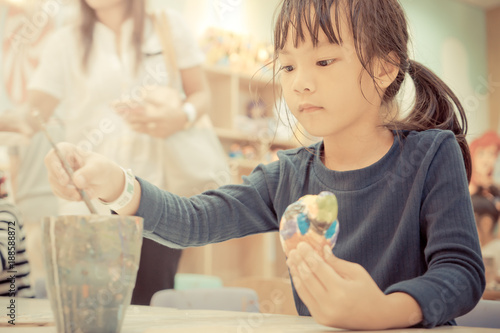 Foto Murales Little girl is painting a doll in art classroom