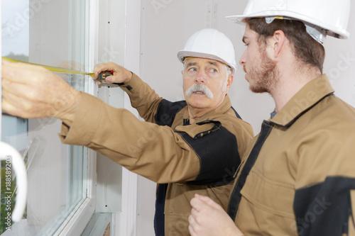 Foto Murales two workers measuring windows