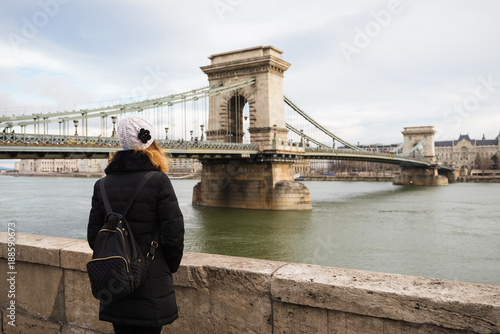 Fotobehang Wit Young woman is looking at the Chain bridge from Danube riverbank by the road in Budapest, Hungary.