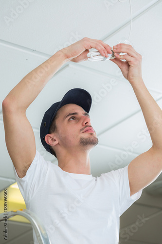 Foto Murales handsome electrician changing lightbulb