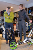 young boy showing a bicycle to friends in sport shop - 188598618
