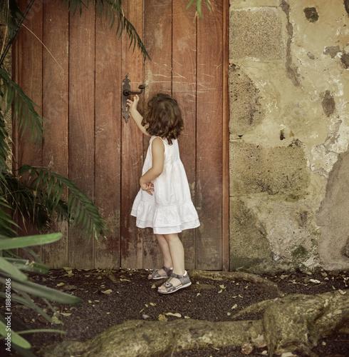 Papiers peints Artiste KB Little girl checking old, wooden door