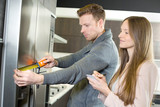 Couple measuring American fridge freezer - 188605622