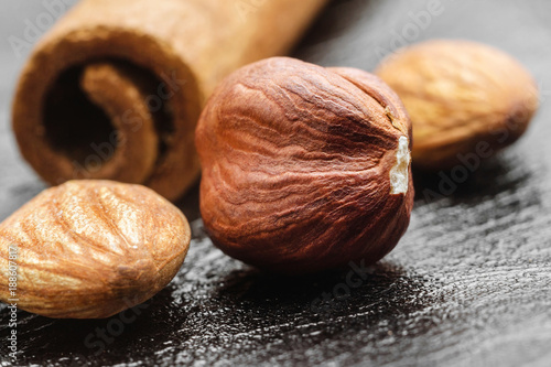 Brown, raw hazelnut kernel,almond nuts and cinnamon stick on black leather texture background, macro image
