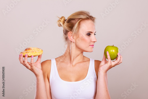 Foto Murales Woman holds cake and fruit in hand choosing