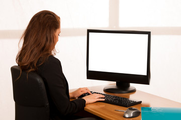 Baeutiful young business woman working at her desk in the office checking data on her monitor screen