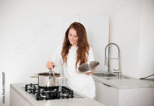 Poster Beautiful young woman in white chef uniform cooking in the kitchen