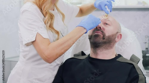 Beautician makes botox injection in forehead to gay © oles_photo