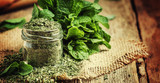 Dried peppermint in a glass jar and a bunch of fresh mint, vintage wood background, selective focus - 188625017