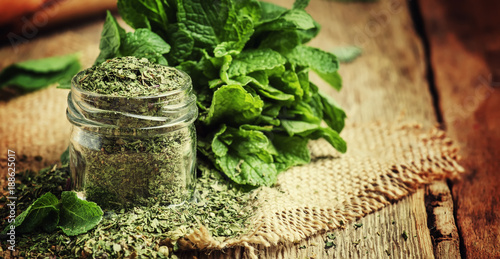 Dried peppermint in a glass jar and a bunch of fresh mint, vintage wood background, selective focus