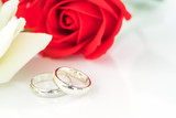 Red rose and wedding ring on white - 188629693