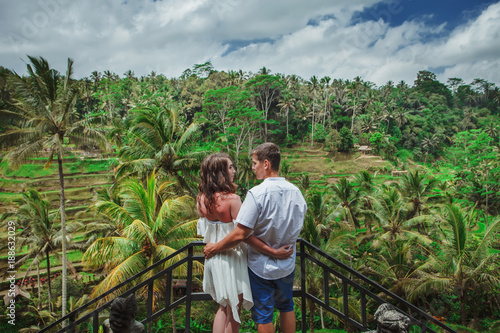 Happy couple walking at the rice terraces. Traveling at Bali.