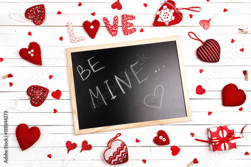 Blackboard with  confession and hearts on white wooden background. Valentine's day concept.