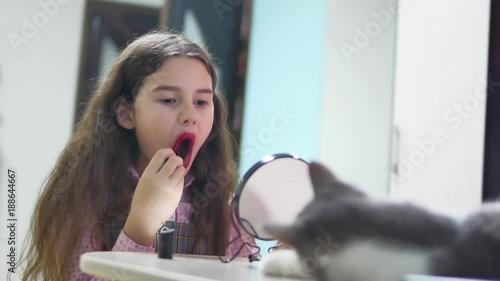 little girl paints lips with indoor lipstick . schoolgirl paints lips teen red lipstick in front of mirror