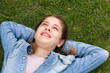 teen using digital tablet while lying in summer park