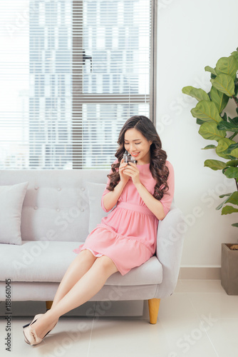 Foto Murales Young beautiful asian woman relaxing in sofa with cup of pure water