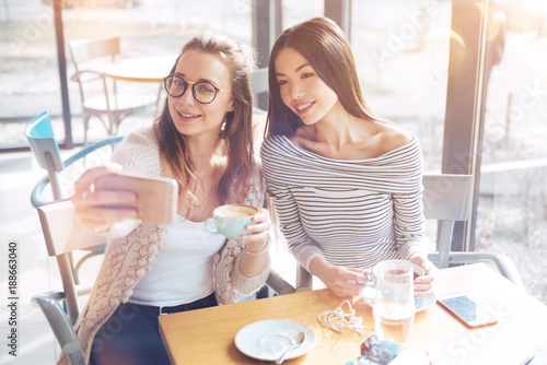 Selfie time. Pretty Korean woman holding cup of tea in both hands and keeping smile on her face while bowing her head to her friend