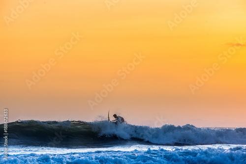 Fototapeta Surfing the waves of Indonesia beach