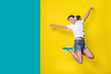 young woman listening music and jumping on yellow background - 188682256