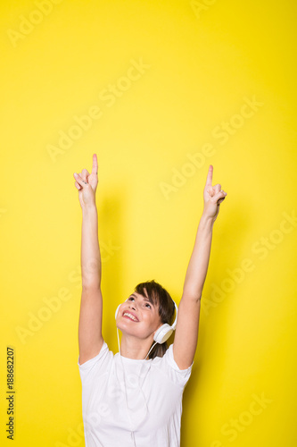 young woman listening music on yellow background - 188682207