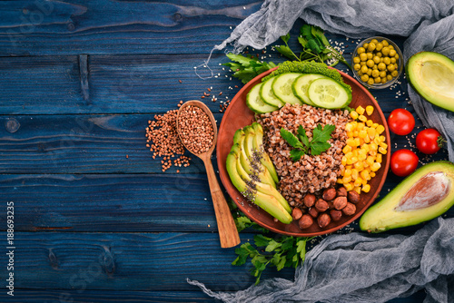 Foto op Canvas Boeddha Healthy food. Buckwheat, avocado, cucumber, corn and hazelnut. On a wooden background. Top view. Free space for your text.