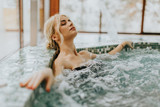 Young woman relaxing in the whirlpool bathtub - 188694650
