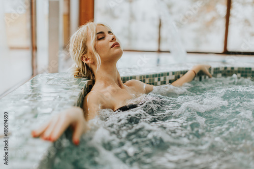 Young woman relaxing in the whirlpool bathtub © Boggy