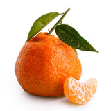A segment of a mandarin next to whole mandarin with leaves isolated on white.