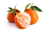 One half peeled and two whole mandarins with leaves isolated on white.