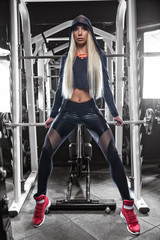 A girl in a weight lifting gym makes exercises using sports equipment in beautiful sportswear.