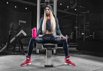 In the gym after a heavy workout, the blonde drinks sports nutrition from a black shaker.