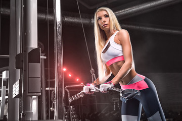 Girl athlete bodybuilder, in beautiful sports clothes, doing exercises in the gym. Personal trainer.