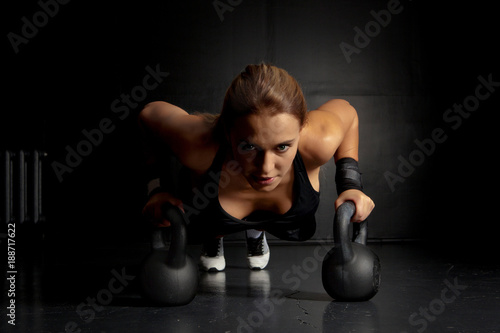 Poster Woman doing push-ups exercises on kettlebells