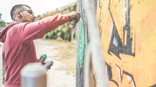 Young street artist painting with color spray on the wall - Contemporary graffiti artist at work - Urban lifestyle, modern street art and youth concept - 188718084