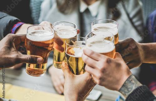 Foto Murales Group of friends enjoying a beer in brewery pub