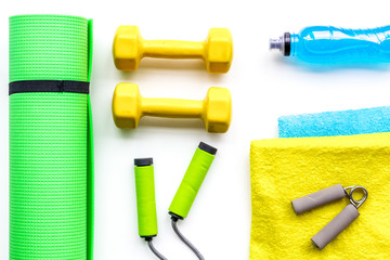 Do fintess in gym. Dumbbells, jump rope, expander, mat, water on white background top view pattern © 9dreamstudio
