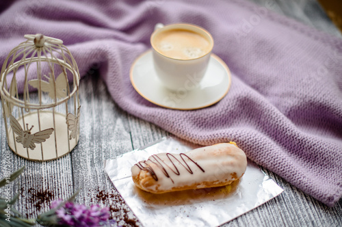 Cup of coffee and sweater on a wooden background