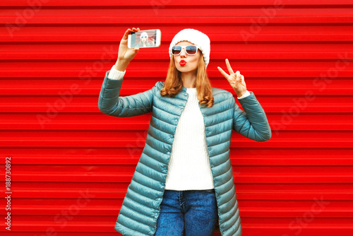 Fashion pretty woman takes a picture self portrait on a smartphone on red background - 188730892