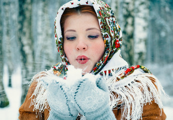 girl in Slavic style in a scarf blows snow from mittens.