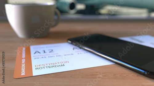 Deurstickers Rotterdam Boarding pass to Rotterdam and smartphone on the table in airport while travelling to Netherlands. 3D rendering
