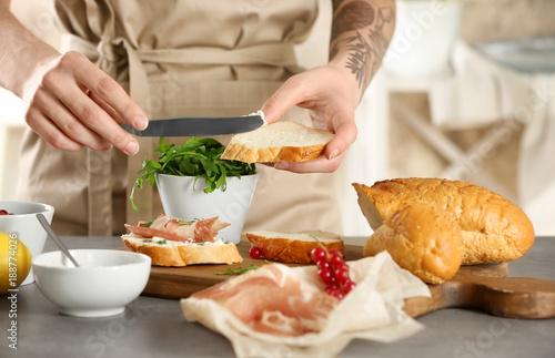 Woman preparing delicious bruschettas on table
