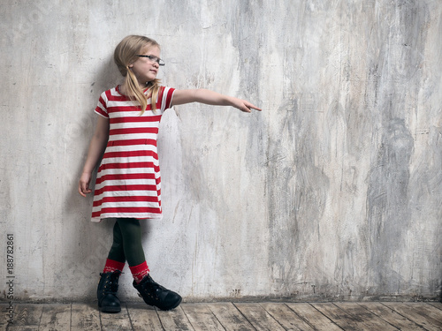 Little girl in glasses makes a pointing hand gesture. Textured grey wall
