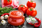 Tomato paste, puree in glass jar and fresh tomatos on dark background. Hot vegetable sauce with chili pepper and tomatoes - 188792230