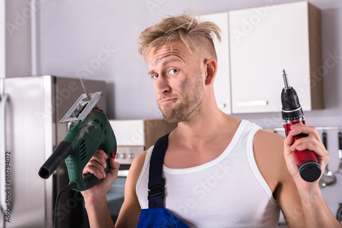 Workman Holding Electric Drill And Screwdriver