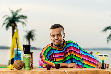 Front view of handsome positive Mexican bartender standing on the bar counter and relaxing at the resort