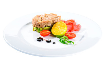 Tasty Tuna Tartare with lime, ginger and avocado in a white plate isolated on white background, close-up