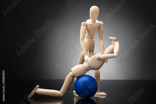Plexiglas Fitness Trainer Assisting Wooden Figurine Exercising On Fitness Ball