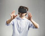 Young man playing in modern VR goggles.