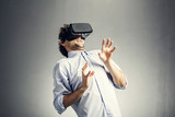 Frightened man playing in VR goggles.